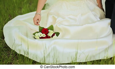 The bride and groom are sitting on green grass with a bouquet