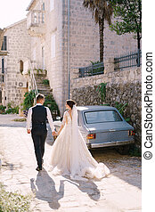The bride and groom are walking along an old stone street, against the background of blue vintage car. Wedding couple holding hands, shadow on the floor. Fine-art wedding photo in Montenegro, Perast.