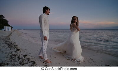 The bride and groom at sunset on a beautiful tropical beach. The bride sensually dances before the groom, holding on to the dress and turning. They are barefoot on the sandy shore of the ocean. Shooting in motion.