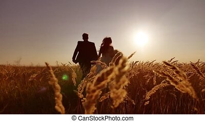 the bride and groom beautiful young couple. run on field with wheat at sunset silhouette of sunlight