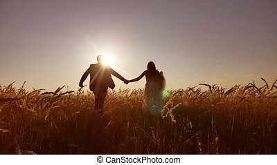 the bride and groom beautiful young couple. run on the field with wheat at sunset silhouette of sunlight