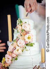the bride and groom cut the cake with fresh flowers
