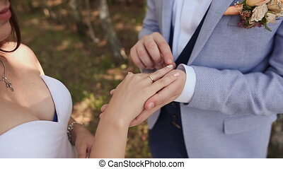 The bride and groom exchange wedding rings against a background of green nature. The groom puts the ring on the arm of his bride close-up. Wedding day.