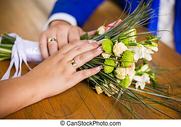 The bride and groom hold hands on a bouquet with rings