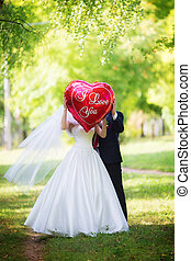 The bride and groom in the Park with the red balloon with...