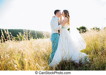 the bride and groom kissing at sunset