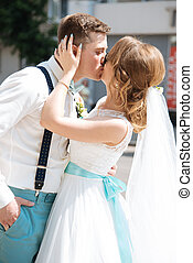 the bride and groom kissing near the registry office - the...