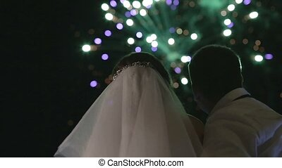 the bride and groom looking at fireworks