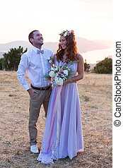 the bride and groom posing at sunset