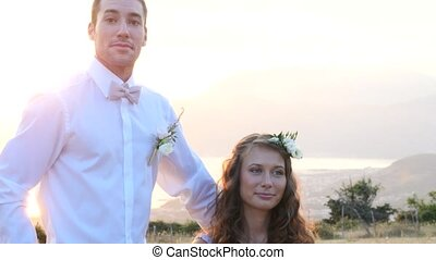 the bride and groom posing on the sunset with a wedding...