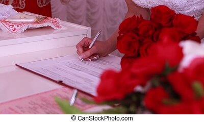 the bride and groom put signatures on wedding ceremony