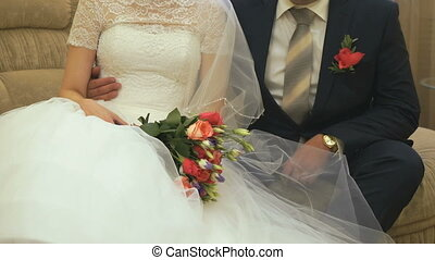 The bride and groom sitting on the sofa in the hall of the...