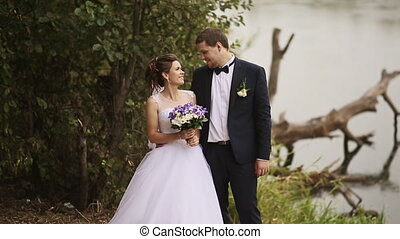 The bride and groom speak near the river and the old tree