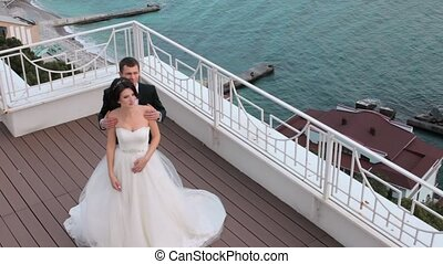 The bride and groom standing on a balcony overlooking the sea