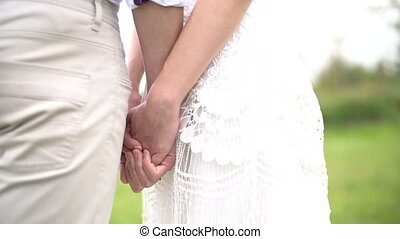 the bride and groom tenderly hold hands. High quality FullHD footage
