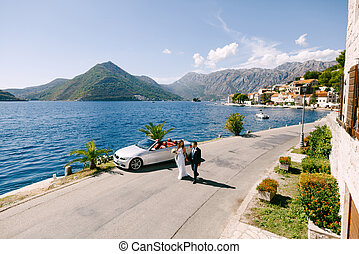 The bride and groom walk holding hands near the car in the old town in the Bay of Kotor