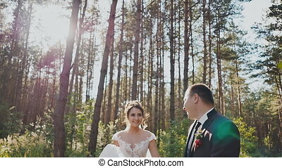 The bride and groom walk in a pine forest, holding hands and looking at each other in the sun. Kiss. Happy together. Wedding day.