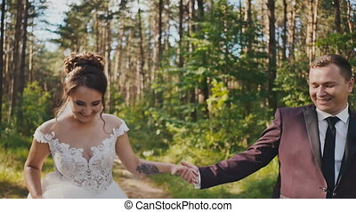 The bride and groom walking in a pine forest, holding hands and looking at each other. Air kiss. Happy together. Walk in the woods on your wedding day.