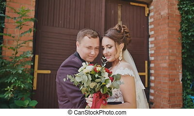 The bride and groom with a bright bouquet in hands together...