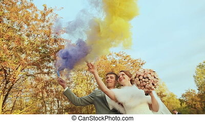 The bride and groom with smoke bombs on the background of trees