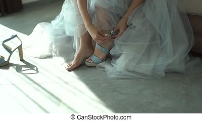the bride buttons up her sandal while preparing for the wedding ceremony. High quality FullHD footage
