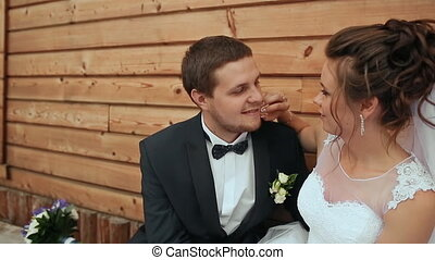 The bride caresses a cheek to the groom and sit on a bench in the old house