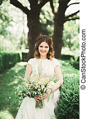 The bride holding bouquet of flowers in park. Wedding