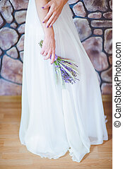 The bride in a wedding dress with a bouquet of flowers.