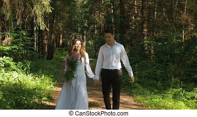 The bride in a white dress and her fianc are strolling through the forest.