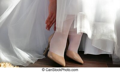 the bride in a white dress puts on her shoes to straighten...