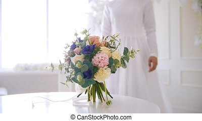 The bride in white wedding dress comes to the flowers