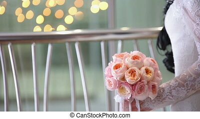 The bride is holding a bouquet of peonies