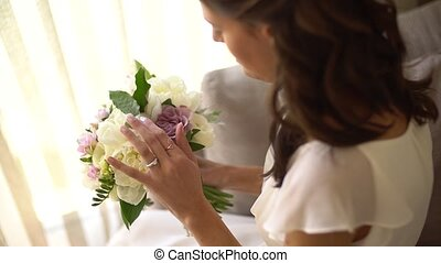 the bride is holding and sniffing the bouquet. High quality FullHD footage