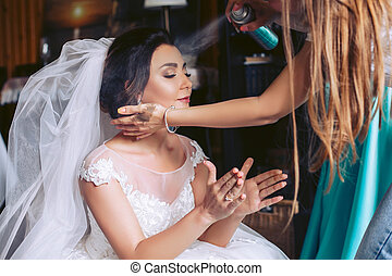 The bride is preparing for the wedding. Hair styling