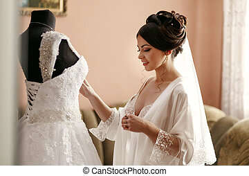 The bride looking at wedding dress