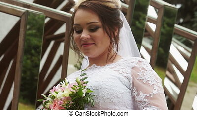 The bride looks at her bouquet