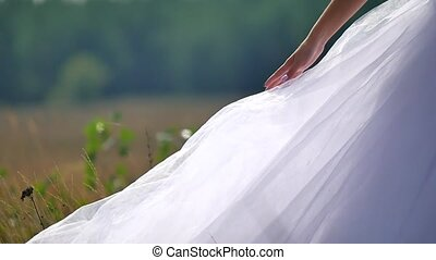 the bride on nature touches the dress with her hand. bride...