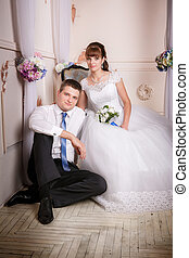 The bride sits in a chair and the groom sits near bride on the floor in the room with a beautiful interior