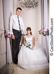 The bride sits in a chair and the groom stands near bride in the room with a beautiful interior