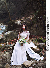 The bride sits on stones high in the mountains near the creek