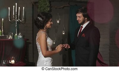 The bride wears a wedding ring to the groom in a fabulous location with candles