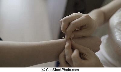 the bride wears wedding jewelry, put bracelet on wrist.