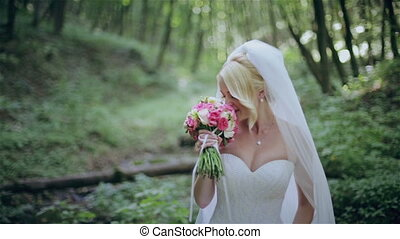 The bride with a bouquet in the wood