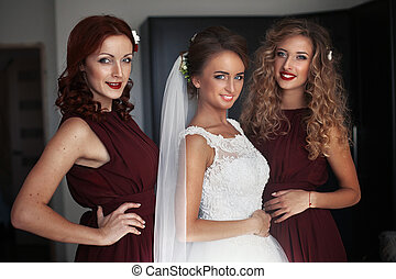 The bride with bridesmaids stands in the center of room