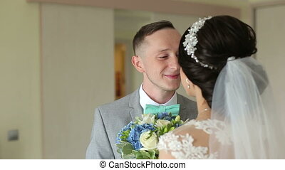 The bridegroom walks into the room to the bride, gives her a bouquet of flowers.
