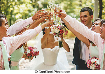 The brides and friends drink glasses of champagne