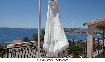 The bride's dress flutters in the wind on the balcony,