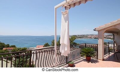 The bride's dress flutters in the wind on the balcony.
