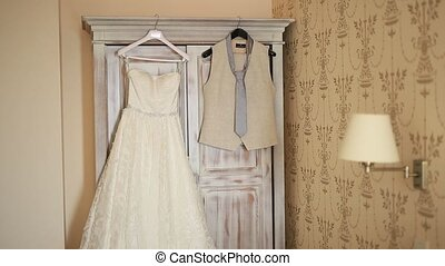 The bride's dress hangs in the apartment. Bridesmaids at the...