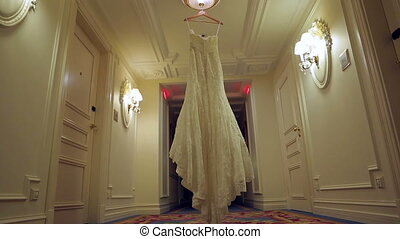 The bride's dress hangs on a hanger in the hall.